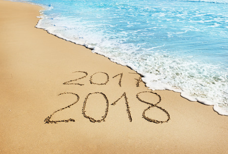 Digits 2017 and 2018 on the sand seashore- concept of New Year and Xmas and passing of time