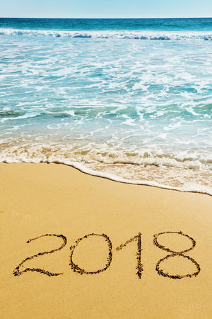 digits  2018 on the sand seashore - concept of New Year and  Xmas