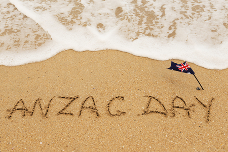 Words Anzac day and Australian flag on the sand of seashore.Lest we forget  Archivio Fotografico