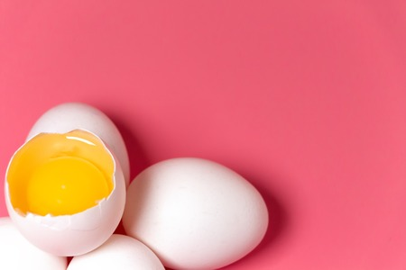 Fresh farm chicken eggs, food background. Cracked egg with white and yolk over pink. Spring easter theme. Close up. Copy space. Stock Photo