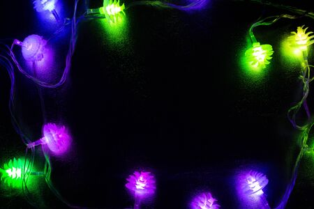 New Year festive garlands glowing in the dark of night on a dark background Stock Photo