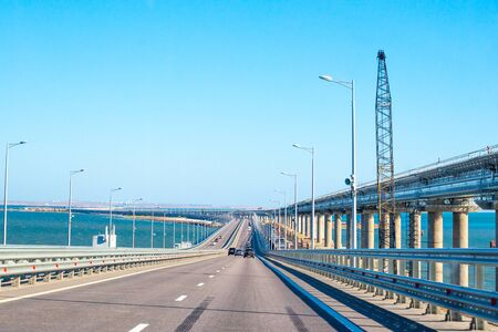Transport passes over the Crimean bridge in Russia, a railway bridge is being built nearby, which will open soon Stock Photo