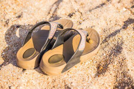 Sandalen stehen an einem heißen Sommertag auf dem Meeressand
