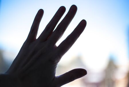 woman's hand outline on the glass of a street window