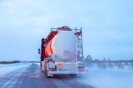 a fuel truck is driving along a road in the north in winter