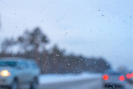 blurred background of car windshield with snowflakes