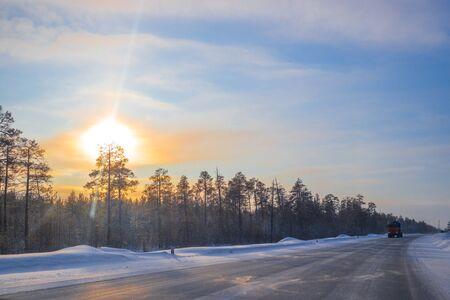Los coches viajan en una carretera de invierno en un día soleado.