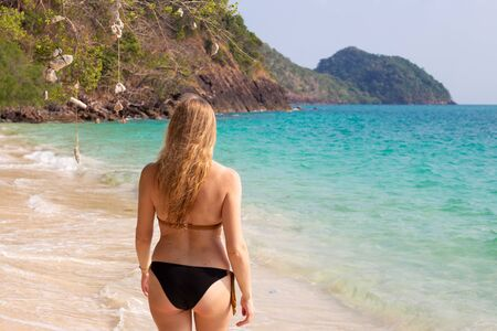 a woman with long hair enters the clear blue sea, real people Reklamní fotografie