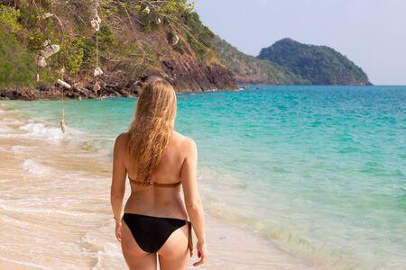 une femme aux cheveux longs entre dans la mer bleu clair, de vraies personnes Banque d'images