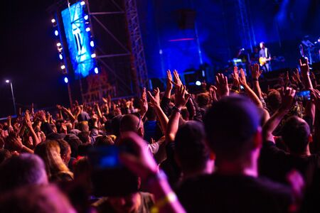 a group of people outdoors dancing at a rock music festival