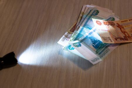 Russian paper money lit by the light of a lantern, the concept of economics and payments