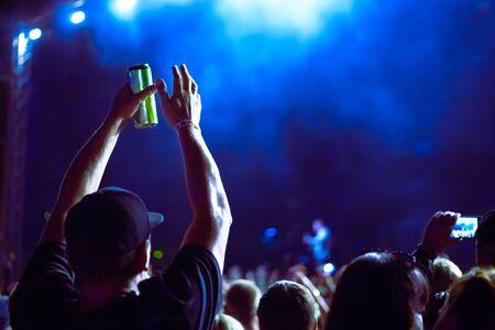 Ein Mann hält eine Dose Bier und klatscht bei einem Musikfestival in die Hände