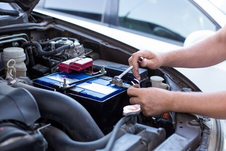 a man tightens with a wrench bolts for fastening a new battery, installing spare parts for a car