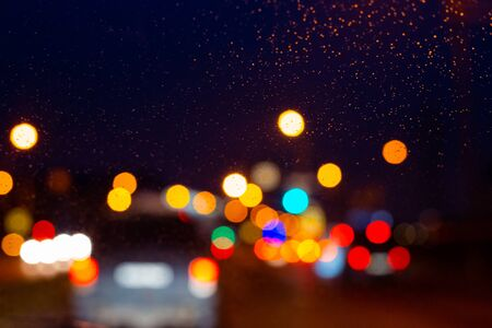 blurry multi-colored lights of illumination on a car glass on a rainy evening, blurred background, copy space