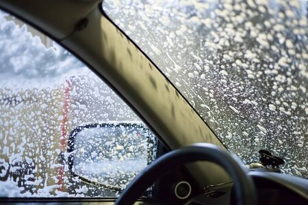car wash, soap foam on glass, view from the passenger compartment 免版税图像 - 143560000