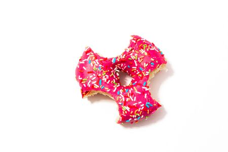 bitten pink donut in the shape of a spinner on a white background, delicious sweet snack