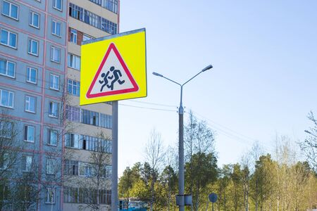 road sign - be careful, children cross the road, on a spring sunny day Banco de Imagens
