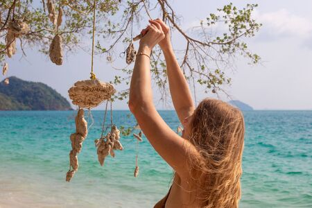 a woman with blond golden hair hangs corals on a wish tree, on the seashore, a dream come true