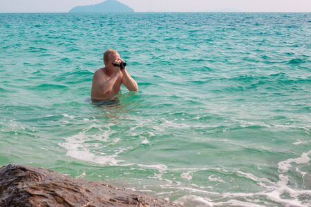 A European man stands chest deep in water and photographs seascapes on a video camera, a blogger prepares materials, travels and tourism