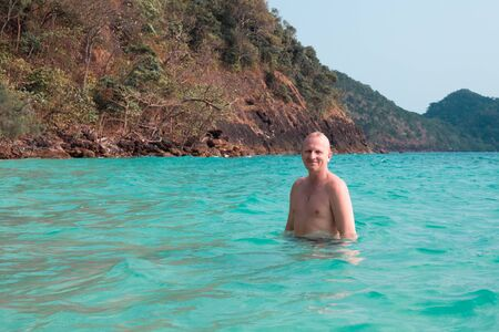 a man bathes in the sea on a background of mountains, smiles with pleasure, summer sea vacation, travel and tourism
