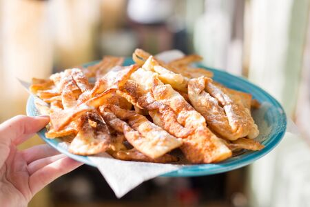 crispy homemade pastry Brushwood lies on a plate in a woman hand,delicious sweet dessert