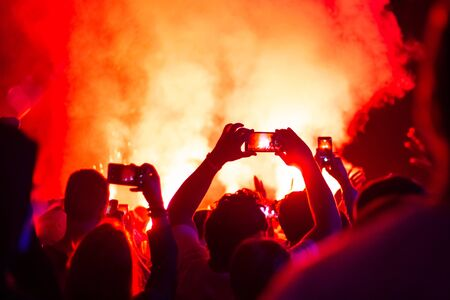 against a background of flame, people at a concert shoot a fire show on the phone
