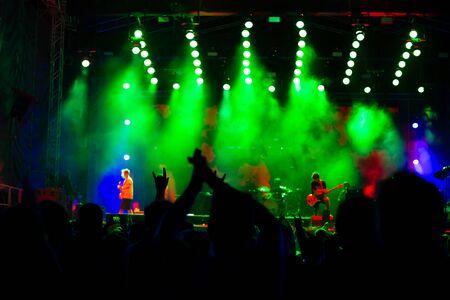 les gens à un concert de musique dansent et applaudissent, festival de rue la nuit, activités de divertissement et de loisirs pour les jeunes, arrière-plan flou