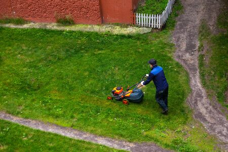 worker mows grass with a mower in the backyard of a house, summer day in the city