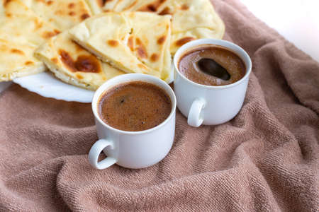 Homemade freshly baked flat bread stuffed with cottage cheese on a table with two mugs of coffee