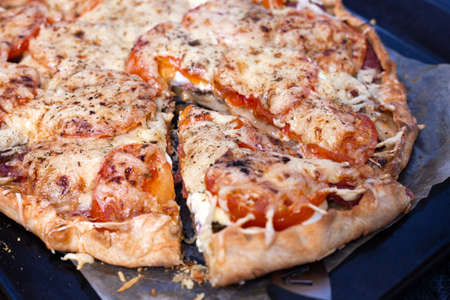 Step 7. Making pizza with sausage. Sliced slice of pizza, lies nearby. Italian cuisine Reklamní fotografie