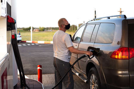 man in a black protective mask refuel a car at a gas station, virus protection