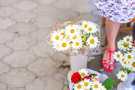 the seller in the market sells flowers. A bouquet of daisies in a vase for sale. Rural street market.