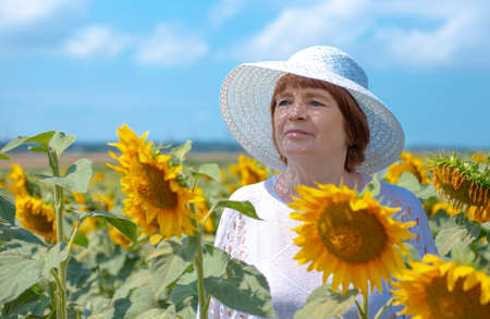an adult woman in a white hat stands in a field with bright flowers of a sunflower against a blue sky. Rural life in the summer in the village.