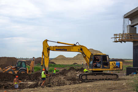 Anapa, Russia-13.07.2020: An excavator digs the ground at the construction of a bridge. Editorial