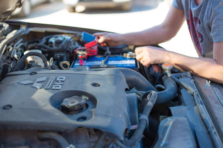 Surgut, Russia-05.10.2020: Repair and replacement of car batteries. The master checks the battery charge. Maintenance of equipment Editorial
