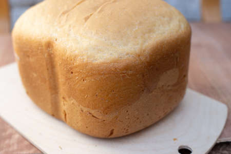 close-up of white bread on a wooden board freshly baked in an electric bread maker. Homemade baking.
