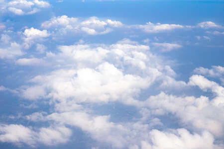 white clouds in the blue sky, top view from an airplane