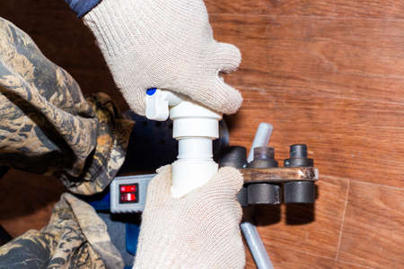 a plumber solders a polypropylene pipe for installing a water supply.
