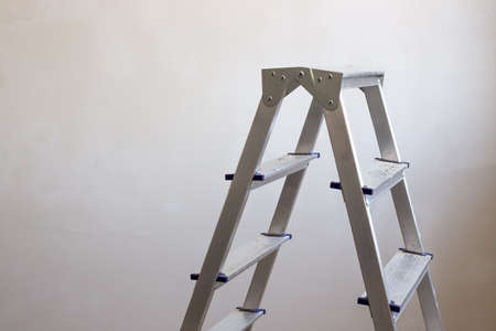 an iron step-ladder stands in a room with gray plastered walls, a copy of the space. Imagens