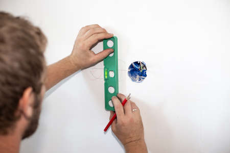 the employee makes the markings for the hole in the wall for the socket. Repair and electrical installation. Copy space.