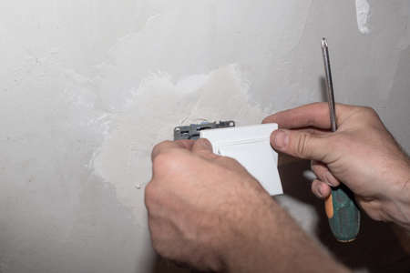 dismantling the socket from the wall. Repair and installation of electrical wiring. Banco de Imagens