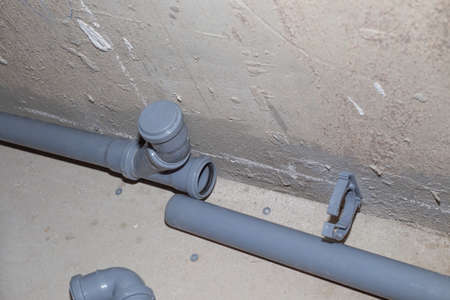 installation of a plastic sewer pipe in the bathroom, repair and construction.