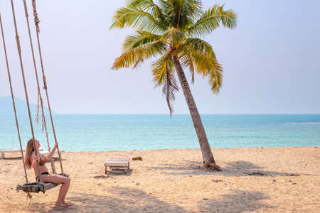 woman in a swimsuit swinging on a swing by the ocean under palm trees, sea vacation and travel. Stok Fotoğraf