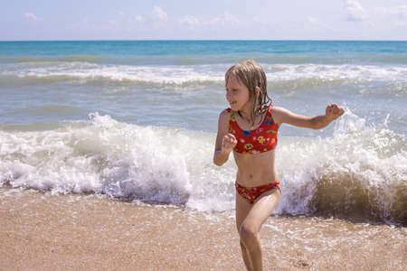 A child in a swimsuit runs out of the water wet. Swimming in the sea, summer vacation, real people.