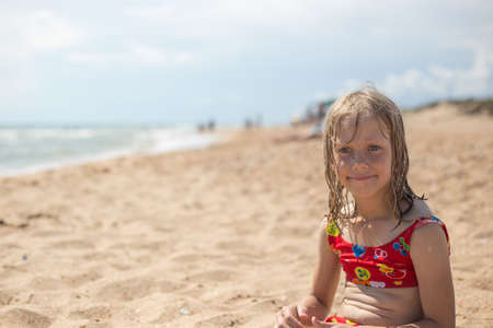 A pensive girl with wet blond hair in a swimsuit sits on the sandy seashore. Summer vacation, travel and tourism.