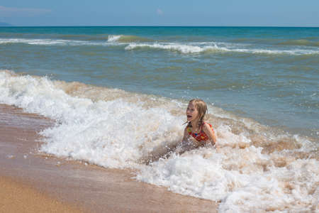 A child in a swimsuit laughs, splashing in the sea waves. Summer vacation at the sea. Banque d'images