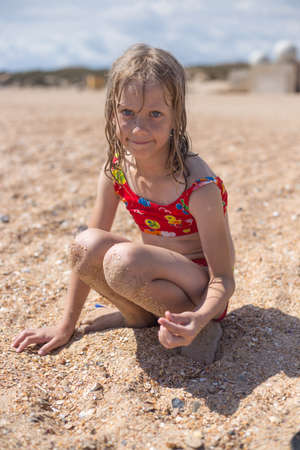 A girl in a swimsuit collects seashells on the sandy seashore. Summer vacation, travel and tourism.