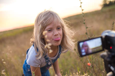The child shows his tongue into the camera lens. Summer blonde girl plays in the meadow. Carefree weekend. Archivio Fotografico