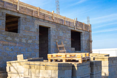 Building a house from cinder blocks. The first floor of the building has been completed. Concrete blocks for construction are on pallets.