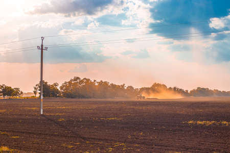 Plowed field in autumn at sunset. In the background, a tractor harrows the soil for sowing winter crops. Agriculture concept.